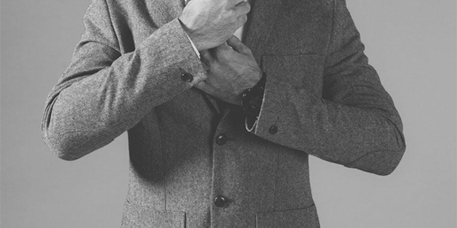 Oberkörper eines Mannes zieht sich eine Krawatte an