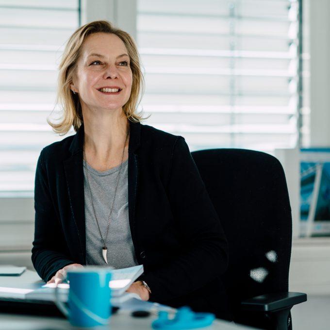 Birgit Jendrock, Projektmanagerin des Unternehmenstags, sitzt an ihrem Schreibtisch und lächelt. Der Blick geht rechts an der Kamera vorbei.