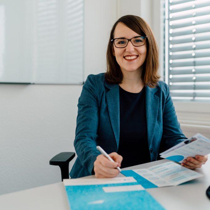 Susanna Mokroß, Eventmanagerin für Forschung und Transfer, sitzt an ihrem Schreibtisch und lächelt in die Kamera.