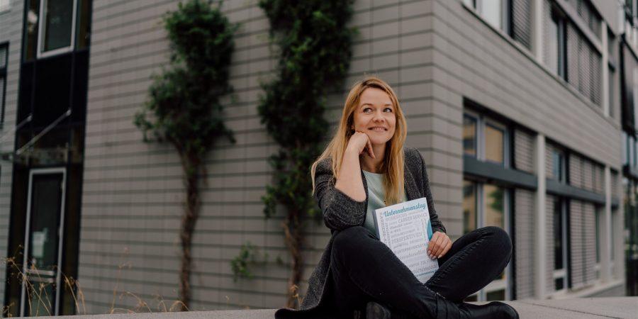 Alumni und Gesicht des Unternehmenstag Patrycja sitzt auf einer kleinen Mauer des Hochschulgeländes. Sie hält das Buch des vergangenen Unternehmenstag in den Händen, in dem alle Aussteller aufgelistet sind, Bilder des Ausstellungstages zu finden und alle weiteren Informationen rund um den Unternehmenstag gesammelt sind.