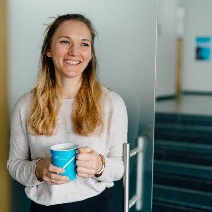 Jana Heberlein ist Projektmanagerin des Forschungs- und Transfermarketing. Mit einer Tasse in Hochschulfarben in der Hand, strahlt sie mit Blick an der Kamera vorbei.
